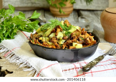 Fried potatoes with chanterelles on rustic background.