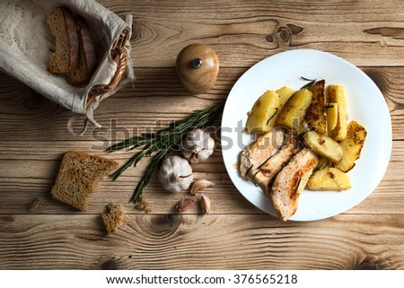 fried potatoes with chicken fillet on a wooden background - stock photo