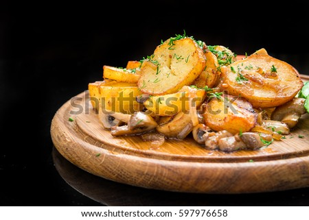Fried potatoes with mushrooms and vegetables on a wooden board