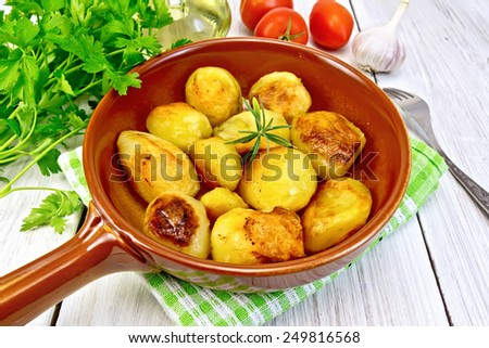 Fried potatoes with rosemary in a ceramic pan on a napkin, garlic, parsley, vegetable oil, tomatoes on a wooden boards background - stock photo