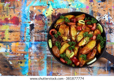 Fried potatoes with sausages, onion rings and green parsley. Meal served in pan on colorful painted table. - stock photo