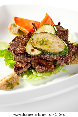 Fried Prime Beef on Salad Leaf Topped with Zucchini - stock photo