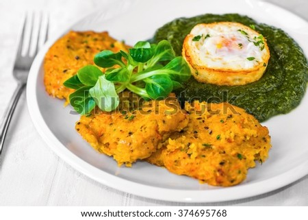 Fried pumpkin pancake with spinach and egg on white plate