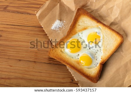 fried quail eggs in a toast on wooden background