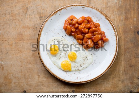 Fried quail eggs with beans, rustic wooden surface, above view - stock photo