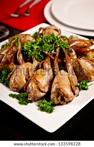 Fried quail with parsley on plate with black background - stock photo