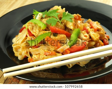 Fried rice noodles with chicken pieces and vegetables - stock photo