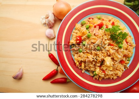 Fried Rice over wooden table background with ingredients with copy space - stock photo