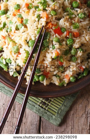 fried rice with egg, peas, carrots close-up on a plate and chopsticks. vertical top view  - stock photo