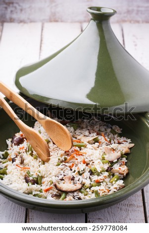 Fried rice with shiitake mushrooms in the tagine.selective focus - stock photo