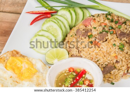 fried rice with vegetables, meat and fried eggs served on a plate with chopsticks - stock photo