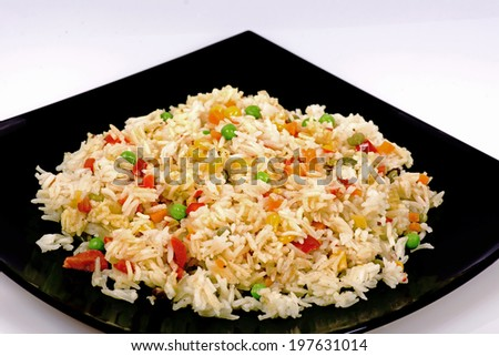 Fried rice with vegetables on a white background - stock photo