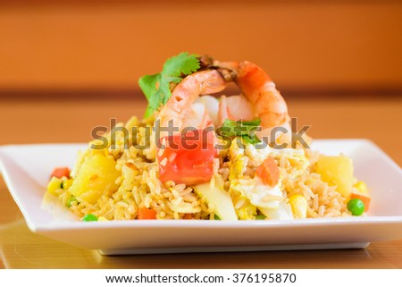 fried rice with yellow curry with shrimp, Thai food on white dish - stock photo