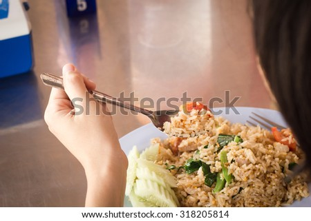 fried rice.Women is eating fried rice.