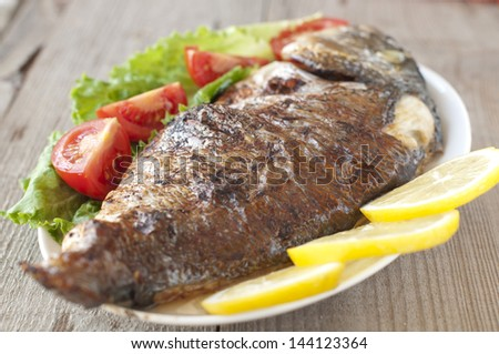 Fried (roasted) Fish (Dorado) Garnished with Lemon, Tomato