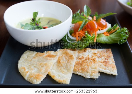 Fried roti, the indian bread, with green curry