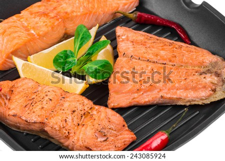 Fried salmon fillet in pan with lemon. Whole background. - stock photo