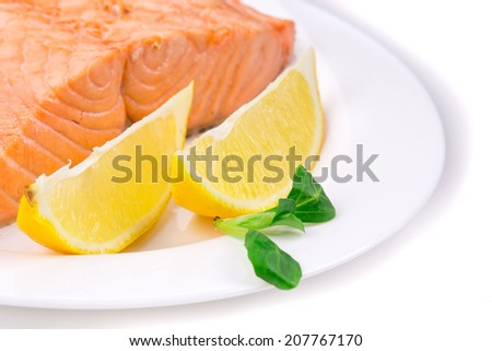 Fried salmon fillet on plate with lemon. Whole background. - stock photo