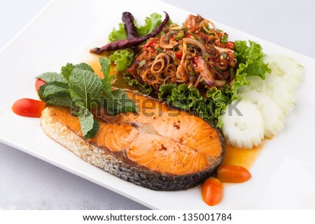 fried salmon fish with spicy salad on whith plate - stock photo