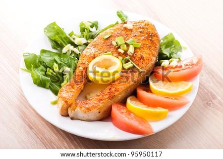 Fried salomon steak on plate in kitchen - stock photo