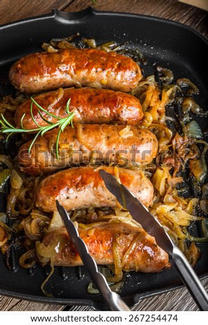 Fried sausage with onion in a pan. - stock photo