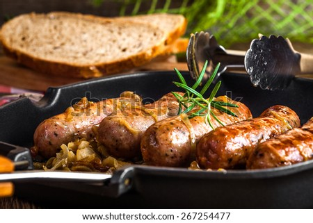 Fried sausage with onion in a pan.