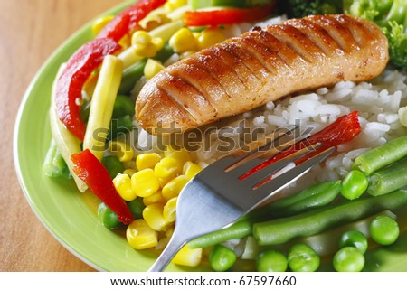 Fried sausage with rice and vegetables - stock photo