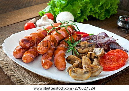 Fried sausages with vegetables on a white plate