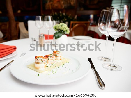 Fried scallops with white asparagus and cream sauce on restaurant table - stock photo
