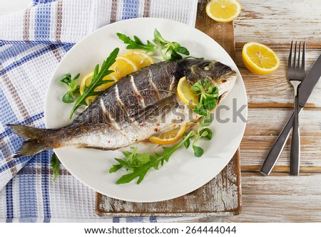 Fried sea bream fish on plate with fresh salad and lemon.  Healthy food. - stock photo