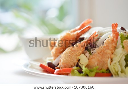 fried shrimp and fresh salad with cream sauce on table