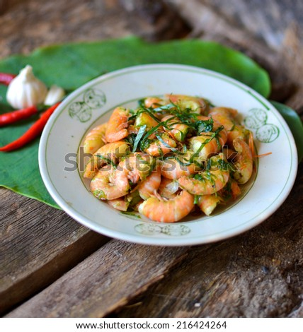 fried shrimp in asia style with ginger leaves on wood table - stock photo
