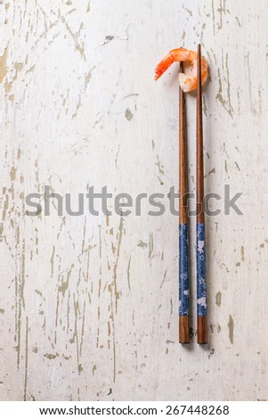 Fried shrimp in dark chopsticks over white wooden background.