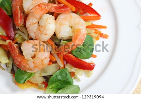 Fried shrimp on a salad of steamed vegetables - stock photo