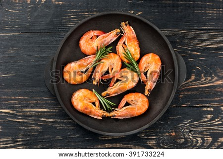 Fried shrimp with rosemary in a portioned frying pan on a dark table top view - stock photo