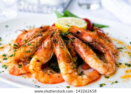 Fried shrimps on a plate with vegetables - stock photo
