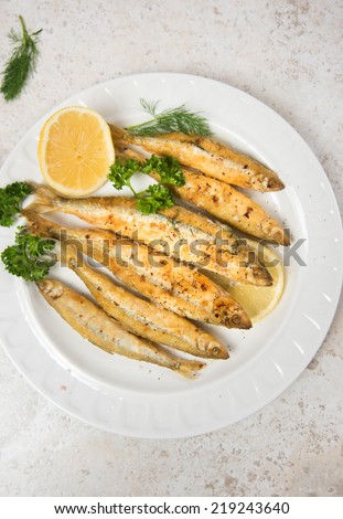 Fried Small Fish Called Smelt Served with Lemon and Herbs - stock photo