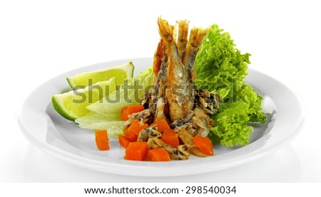 Fried small fish on plate with lettuce and lime isolated on white - stock photo