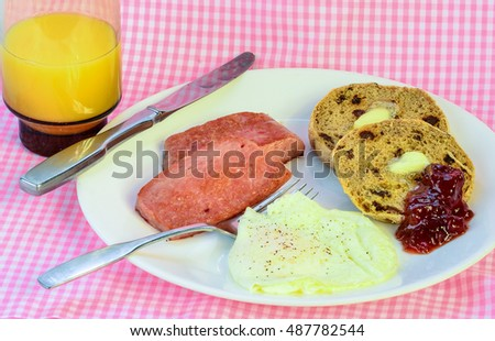 Fried spam with egg over easy and grape jam on cinnamon raisin muffin.  Served with orange juice on pink gingham background.