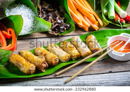 Fried spring rolls surrounded by ingredients - stock photo