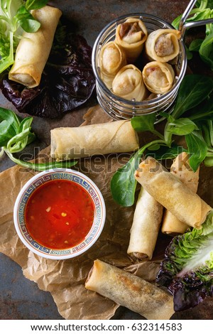 Fried spring rolls with red pepper sauce, served on crumpled paper and in fry basket with fresh green salad over old metal texture background. Top view. Asian food