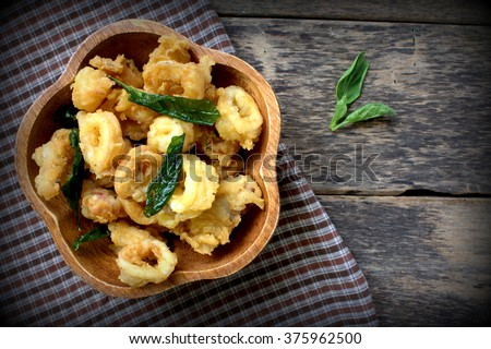 fried squid with basil  on wooden bowl. wooden table  - stock photo