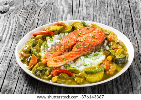fried steak of red fish with rice and homemade curry with zucchini, eggplants, carrots, bell pepper, green beans and chickpeas on a white dish, on an old wood rustic table