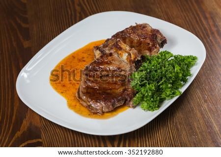 Fried steak on a white plate with salad - stock photo
