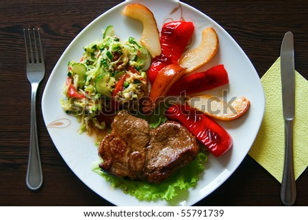 fried steak served with paprika, pear and fresh vegetable salad