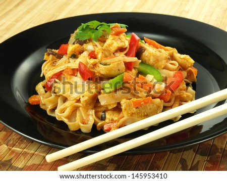 Fried tagliatelle, chicken breast and vegetables in chinese dish - stock photo