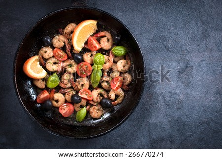 Fried tiger shrimps with ingredients in the pan from above on dark background with blank space - stock photo