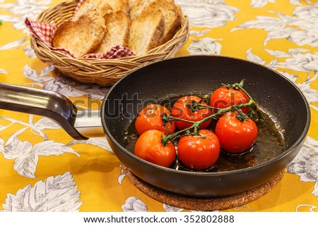 fried tomatoes on the pan with the backgroud of bread in the basket - stock photo