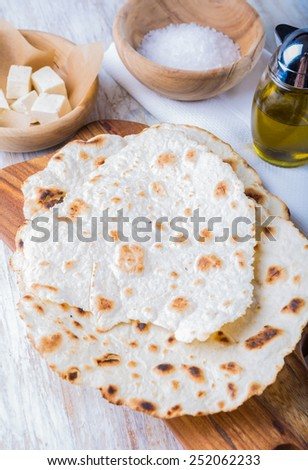 Fried tortilla with cheese on olive wood plate on white background