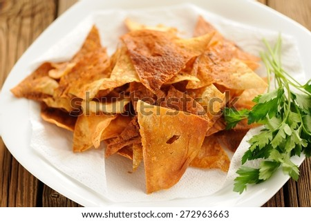 Fried triangle lavash chips in white plate with fresh parsley
